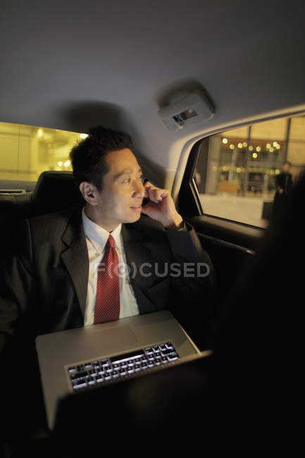 Businessman sitting in back seat of car — Stock Photo