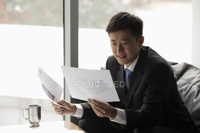 Businessman in suit looking at papers — Stock Photo