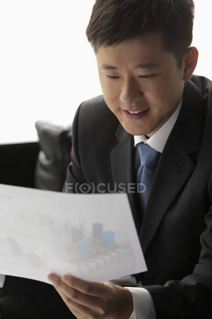 Бізнесмен, дивлячись на шматок паперу — стокове фото