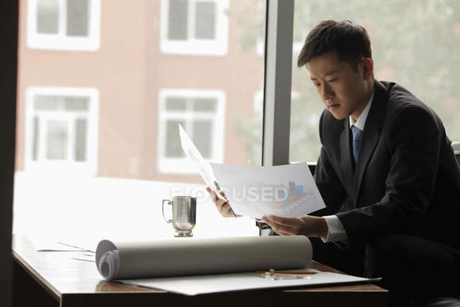Hombre de negocios trabajando con planos - foto de stock