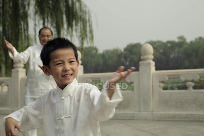 Хлопчик і літня людина робить Tai Chi — стокове фото