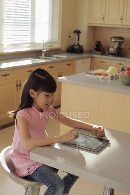 Asiática chica juega en digital tablet - foto de stock