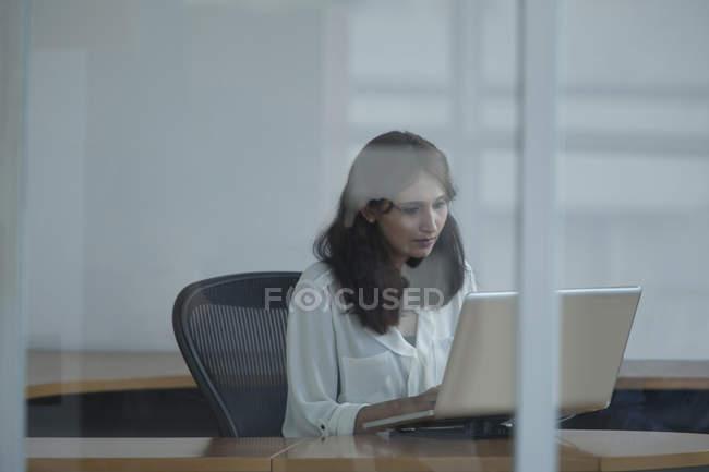 Femme d'affaires utilisant un ordinateur portable dans le bureau — Photo de stock