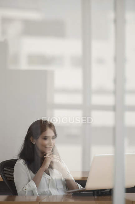 Businesswoman using laptop in office — Stock Photo