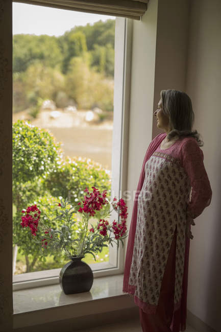 Зрелая женщина, выглядывающая в окно — стоковое фото