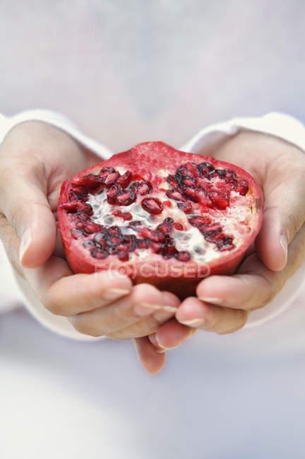 Hands holding pomegranate — Stock Photo