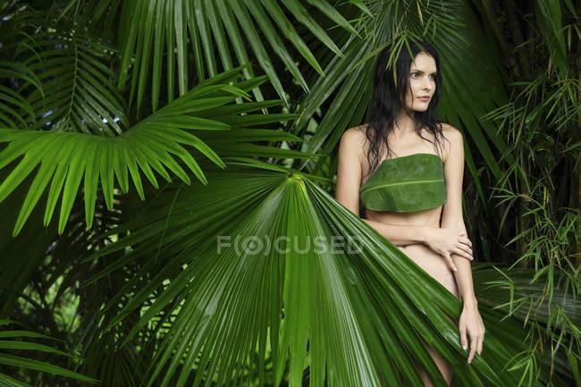 Femme derrière de grandes feuilles tropicales — Photo de stock