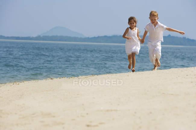 Glückliche Kinder, die laufen am Strand — Stockfoto