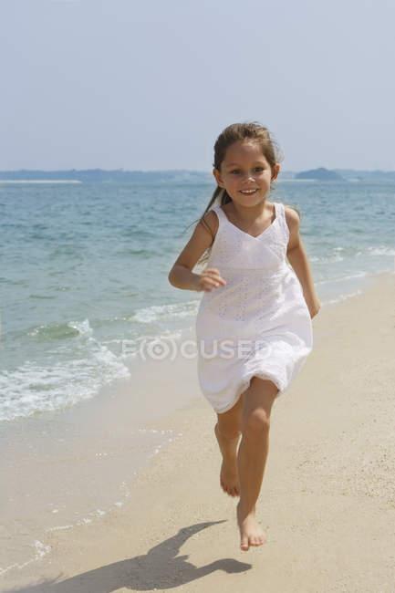 Kleines Mädchen läuft am Strand — Stockfoto