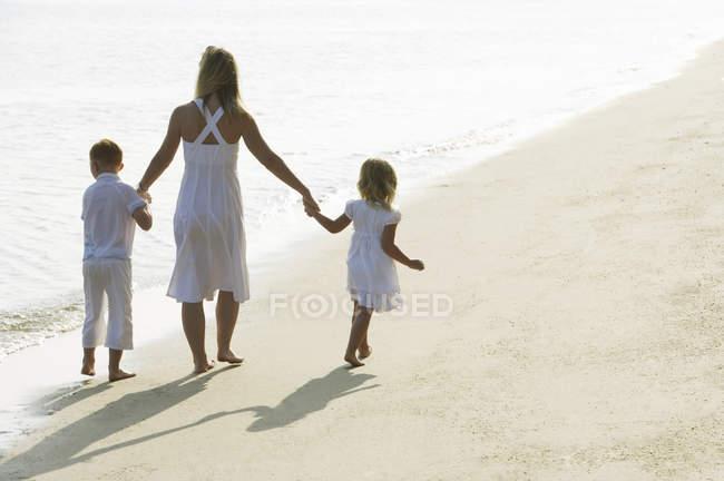 Frau mit Kindern am Strand — Stockfoto