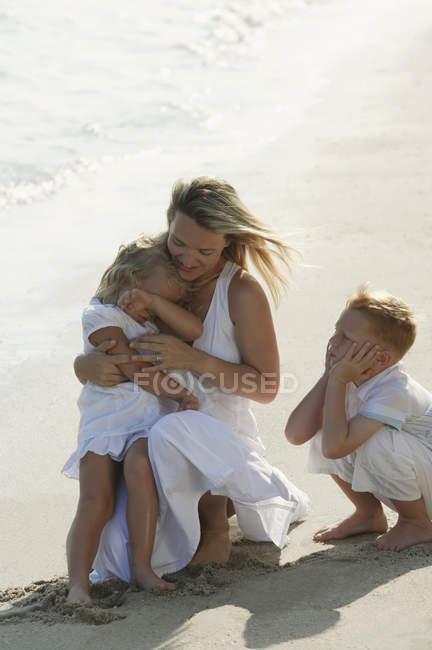 Mulher com filhos na praia — Fotografia de Stock