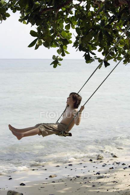 Boy swinging near ocean — Stock Photo