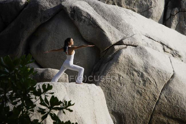 Woman doing yoga on rock — Stock Photo