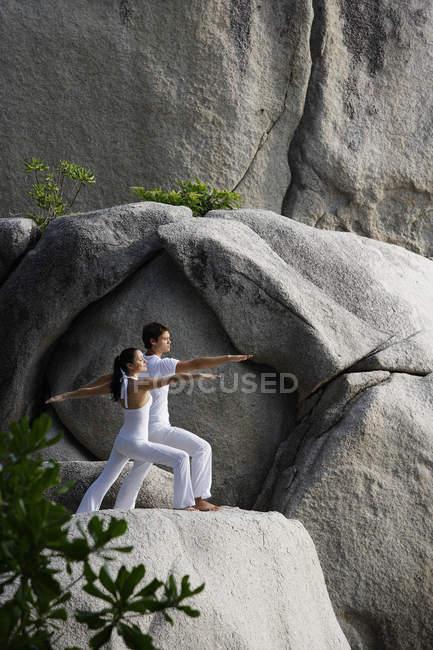 Пара, занимающаяся йогой на скале — стоковое фото