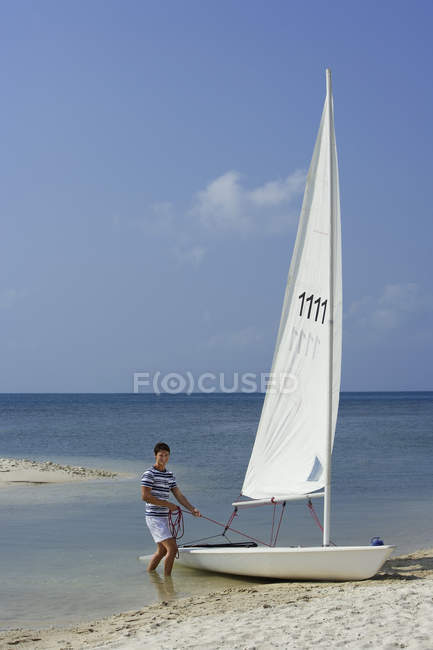 Man with sailboat at beach — Stock Photo