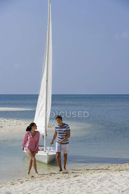 Couple with sailboat on beach — Stock Photo