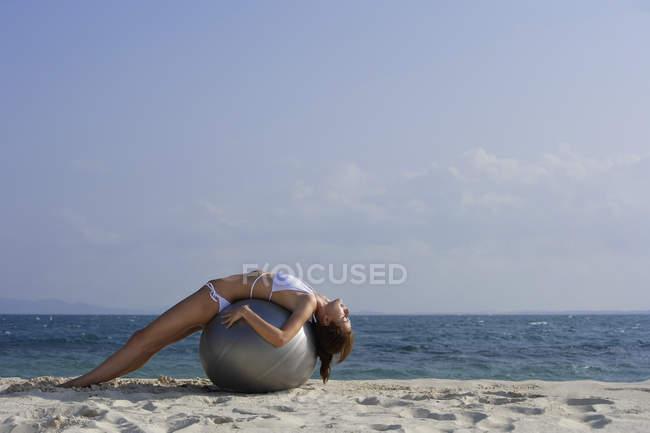 Woman in bikini lying on ball — Stock Photo