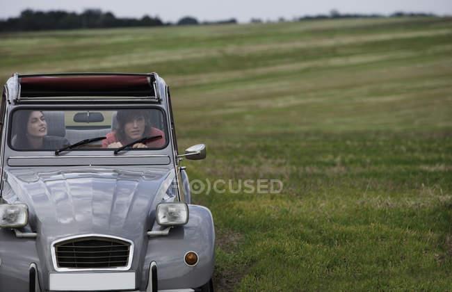 Pareja de conducción de coches de época clásica - foto de stock