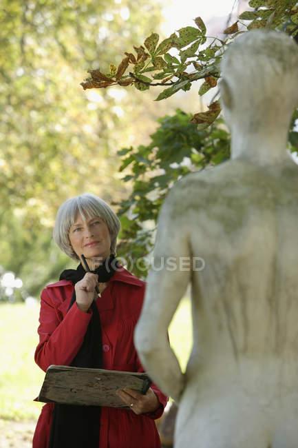 Mujer mayor ponderando estatua - foto de stock