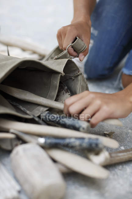 Woman picking up tools in art studio — Stock Photo