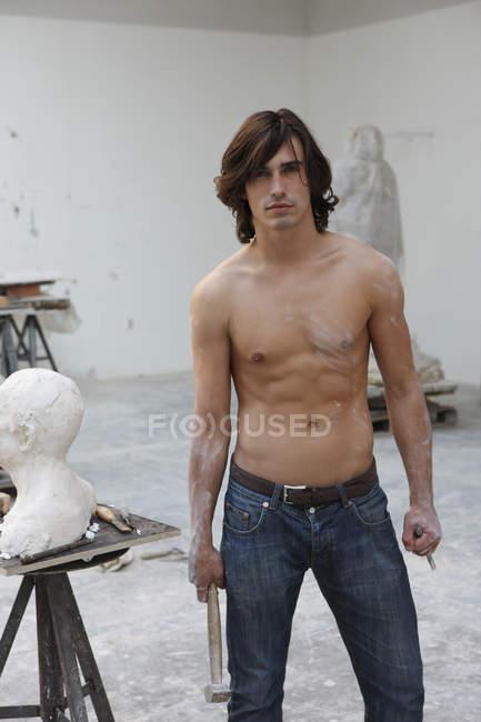 Людина з молотка стоїть біля скульптури — стокове фото