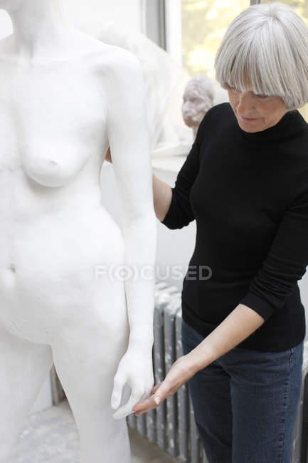 Жінка, торкаючись скульптура — стокове фото