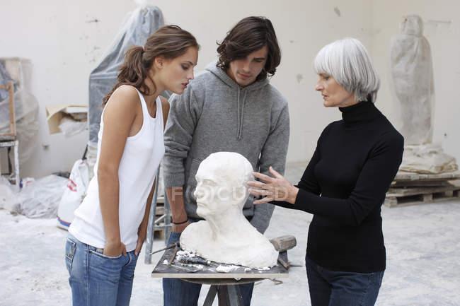 Викладач мистецтва зі студентами в студії — стокове фото