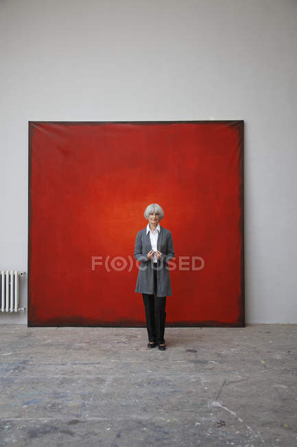 Woman standing in art studio on red background — Stock Photo