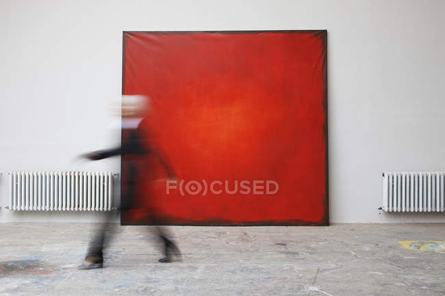 Woman walking by red painting — Stock Photo