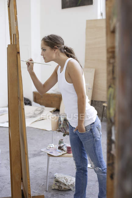 Young woman working on painting — Stock Photo