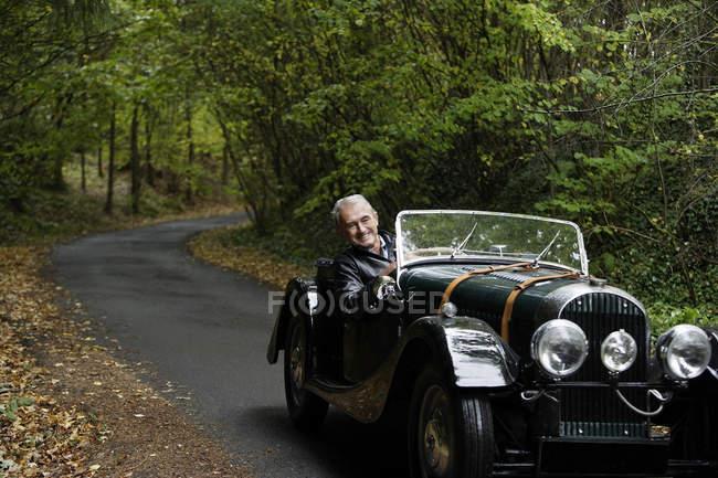 Man sitting at vintage car — Stock Photo