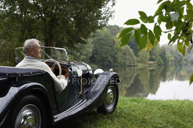 Uomo seduto a auto d'epoca — Foto stock