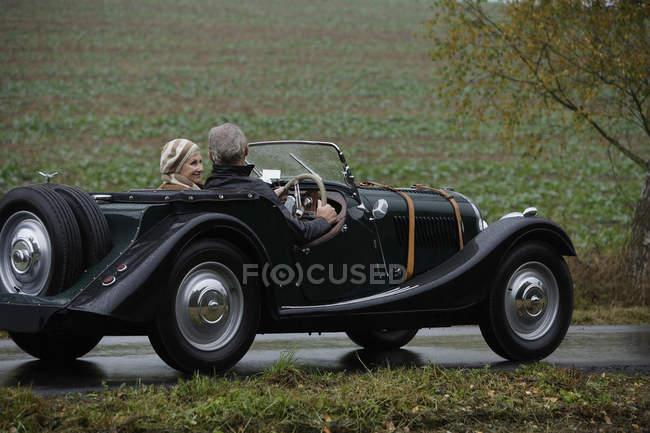 Senior pareja conduciendo en coche antiguo - foto de stock