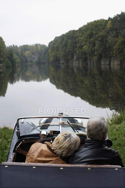 Senior couple driving in antique car — Stock Photo