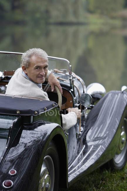 Hombre sentado en el coche de época - foto de stock