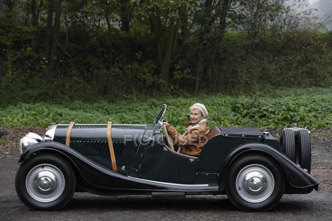 Coche antiguo motor mujer Senior - foto de stock
