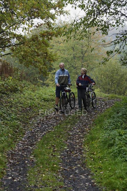 Старшая пара прогулки на велосипедах — стоковое фото