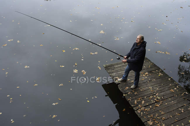 Man fishing on lake from pier — Stock Photo