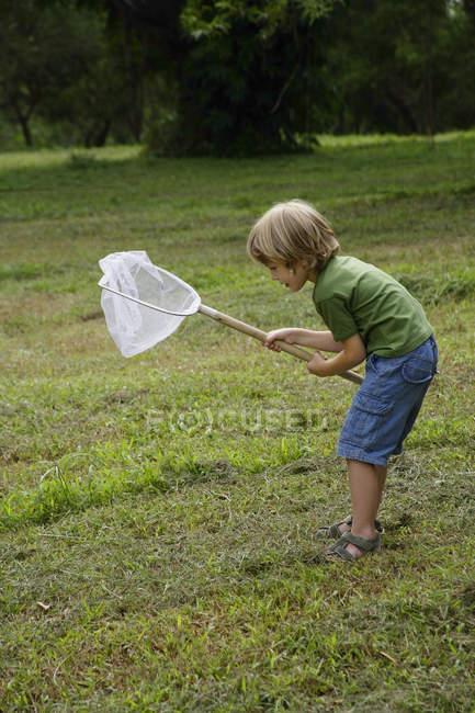 Мальчик держит в руках сетку для бабочек — стоковое фото