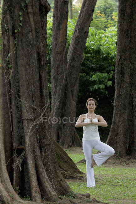 Woman doing yoga exercises under trees — Stock Photo