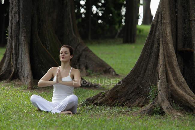 Woman doing yoga exercises under trees — Stock Photo