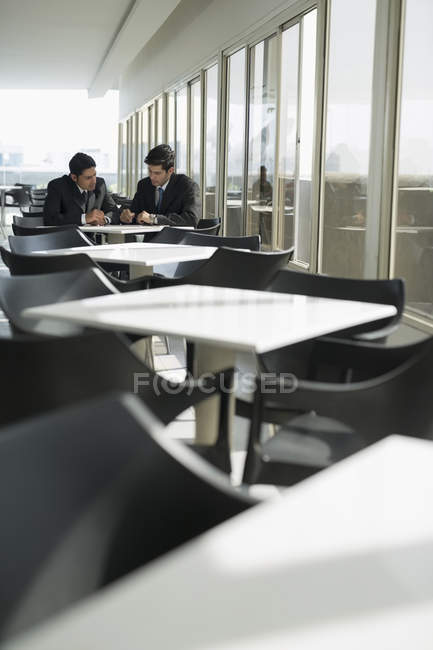 Colleagues sitting in cafeteria and having conversation — Stock Photo