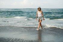 Smiling woman walking on beach — Stock Photo