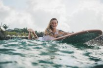 Woman laying on surf board — Stock Photo