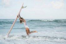 Femme tenant la planche de surf sur la plage — Photo de stock