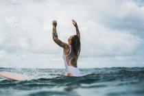 Woman sitting on surf board — Stock Photo