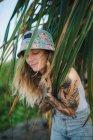 Mujer en arbustos verdes tocando hojas - foto de stock