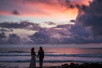 Vue arrière du jeune couple main dans la main, debout sur la plage avec ciel coucher de soleil en arrière-plan — Photo de stock
