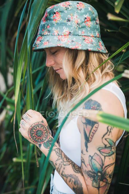 Femme dans les buissons verts avec les yeux fermés — Photo de stock