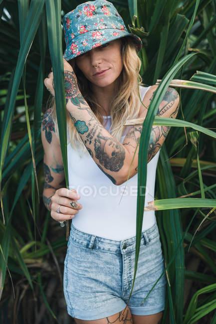 Woman in green bushes looking at camera — Stock Photo